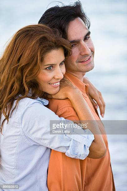 Young Hispanic couple embracing by ocean.