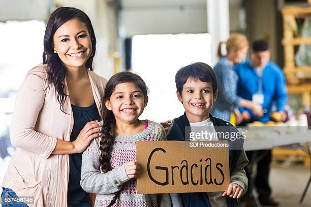 Young Hispanic family holding GRACIAS sign