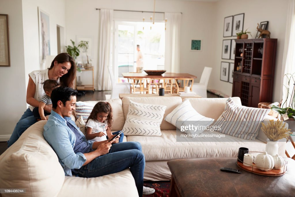 Young Hispanic family sitting on sofa reading a book together in their living room : Stock Photo
