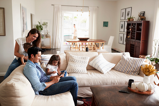 Young Hispanic family sitting on sofa reading a book together in their living room 1094435244