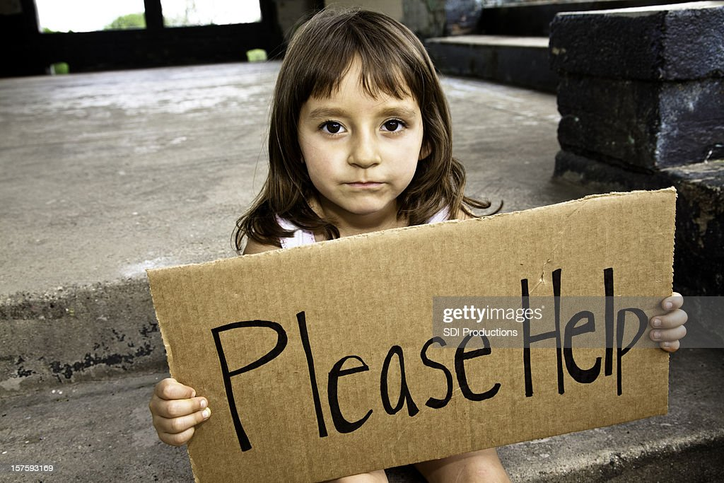 Young Hispanic Girl Holding a Please Help Sign : Stock Photo