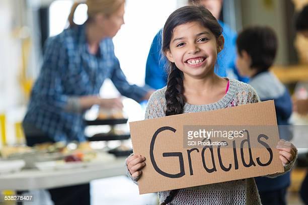 Young Hispanic girl holding GRACIAS sign at charity soup kitchen