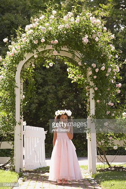 Young Hispanic girl in fancy dress standing under flowered archway