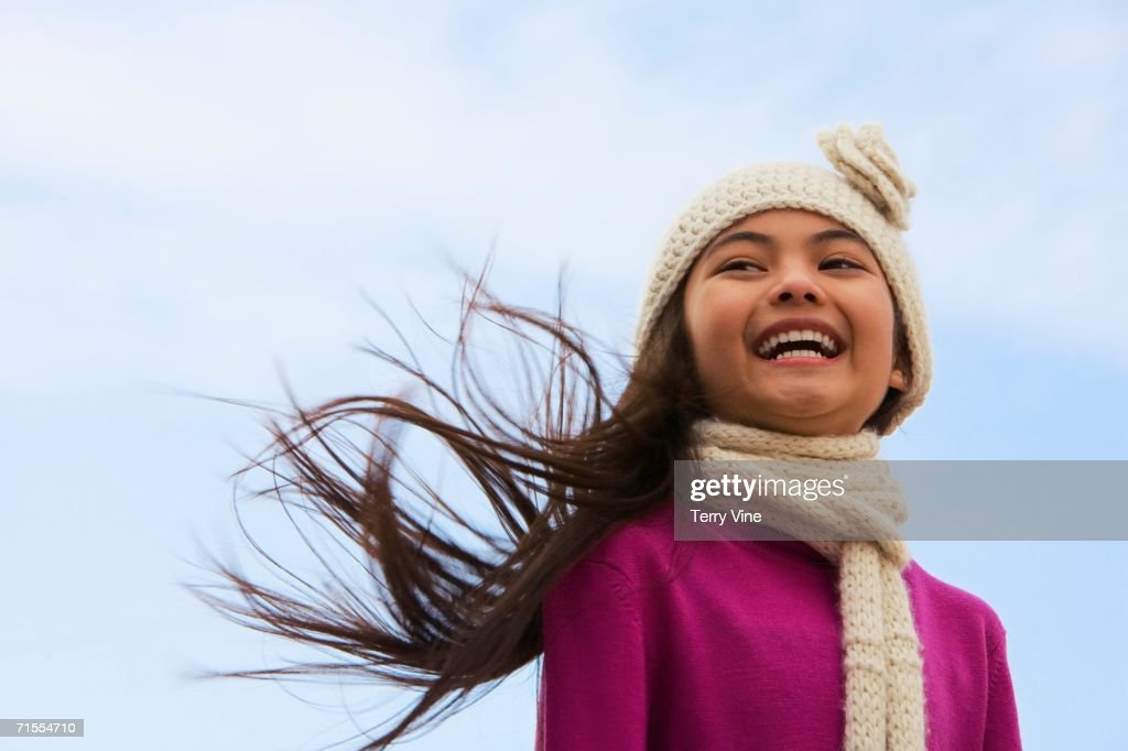 Young Hispanic girl wearing hat and scarf outdoors : Stock Photo