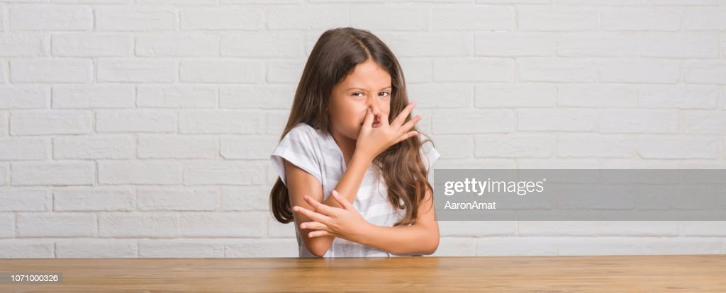 Young hispanic kid sitting on the table at home smelling something stinky and disgusting, intolerable smell, holding breath with fingers on nose. Bad smells concept. : Stock Photo