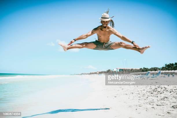 jonge spaanse man doen splitst tijdens de sprong op cubaanse strand - split acrobatiek stockfoto's en -beelden