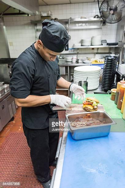 ヒスパニックキッチンで働く若い男性の準備、チーズバーガー