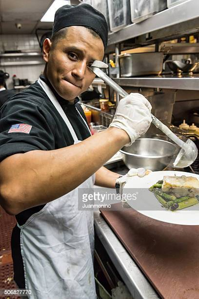 Young hispanic male kitchen worker working