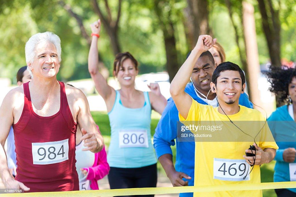 Young Hispanic man celebrating finishing marathon race : Stock Photo