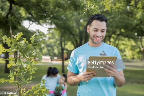 young hispanic man is leading group of volunteers to plant trees in public park - selfless stock pictures, royalty-free photos & images
