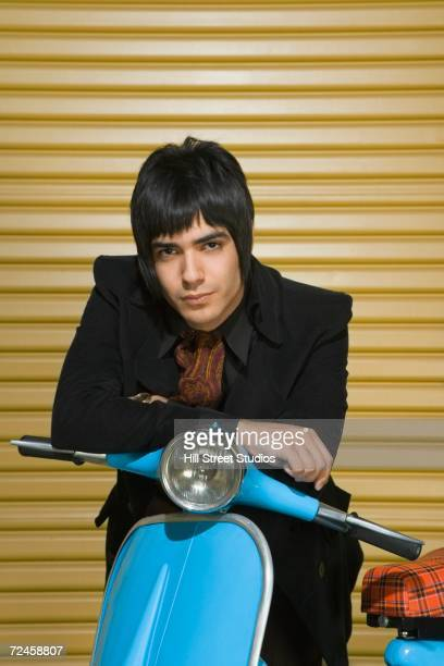 Young Hispanic man leaning on scooter