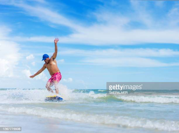 young hispanic man on skim board - fort myers stock pictures, royalty-free photos & images