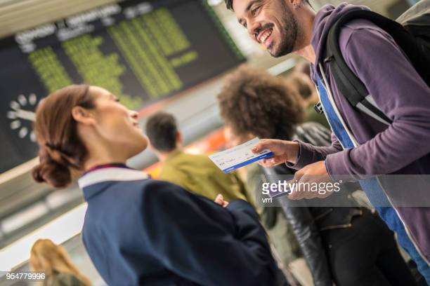 Young hispanic man talking to airport attendant