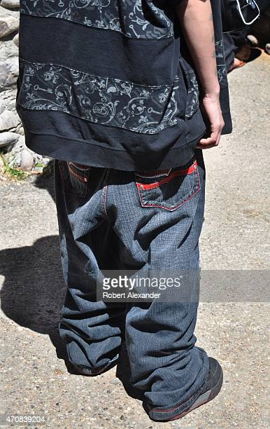 A young Hispanic man wearing baggy low hanging denim pants in the 'hiphop' fashion visits the historic Santuario de Chimayo Catholic church and...