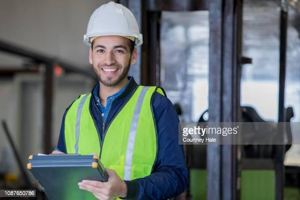 hombre joven hispana trabajando como operador de montacargas en sonrisas de gran almacén al usar equipo de seguridad - conductor oficio fotografías e imágenes de stock