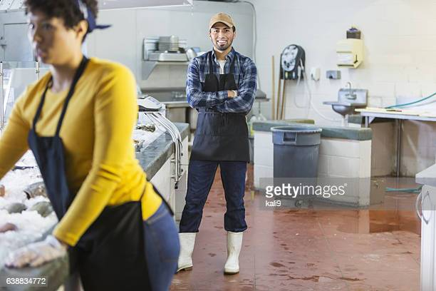 Young Hispanic man working in seafood market