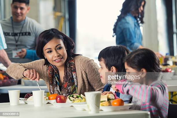 Young Hispanic mother and children eating meal in soup kitchen