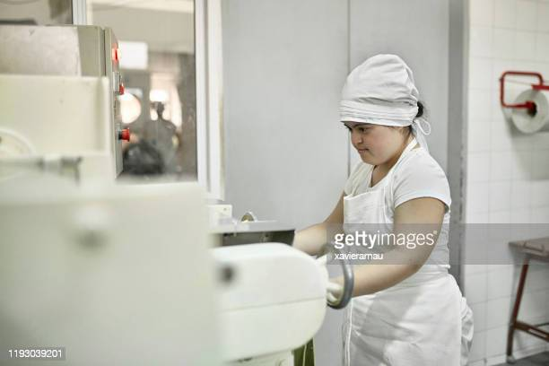 young hispanic pasta maker operating machinery in factory - pessoas com deficiência imagens e fotografias de stock