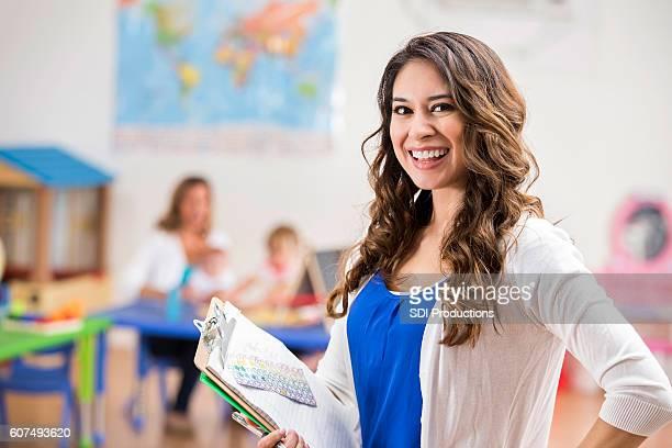 Young Hispanic teacher smiles in classroom