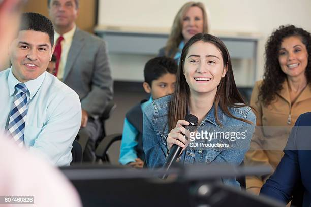 young hispanic woman asks question during town hall meeting - town hall meeting stock photos and pictures