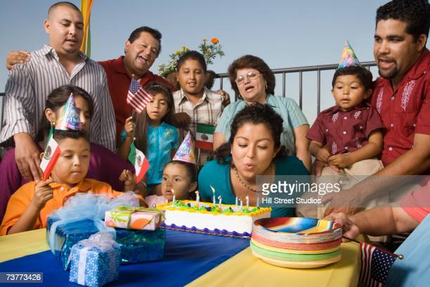 Young Hispanic woman blowing out candles on birthday cake with family