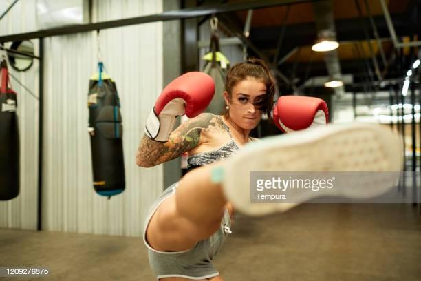 junge hispanische frau, die in einem box-fitnessstudio trainiert und in die kamera tritt. - treten stock-fotos und bilder