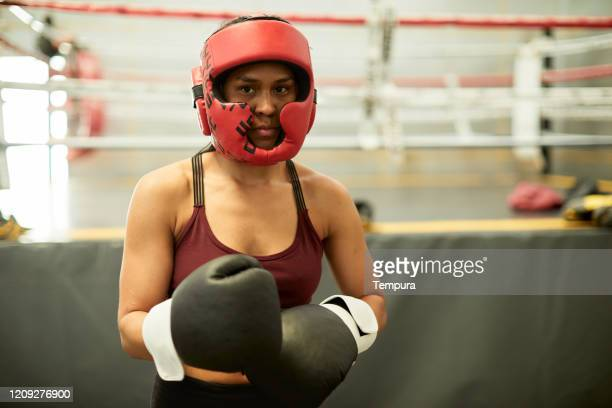 young hispanic woman exercising in a boxing gym wearing a protective helmet. - headwear stock pictures, royalty-free photos & images