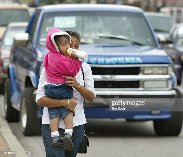 A young Hispanic woman holding an infant child walk along the street September 22 2003 in Chicago's mainly Hispanic Little Village neighborhoodThe US...