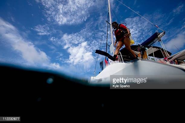 a young hispanic woman in scuba gear jumps off a catamaran. - st. kitts stock photos and pictures