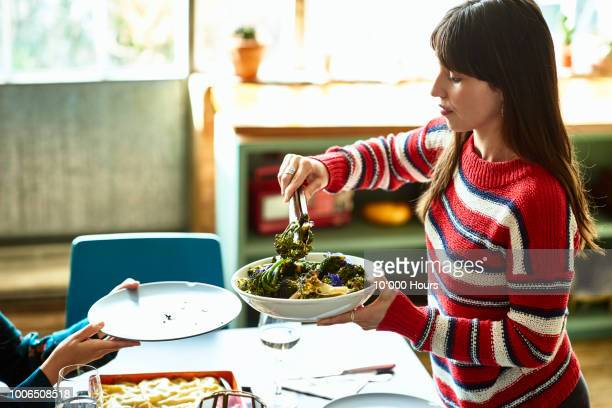Young Hispanic woman in striped sweater serving food from bowl
