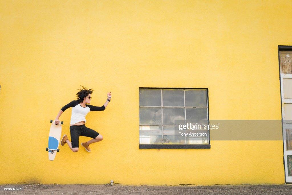 Young Hispanic woman jumping near yellow wall with skateboard : Stock Photo