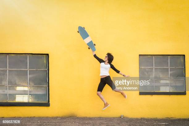 Young Hispanic woman jumping near yellow wall with skateboard