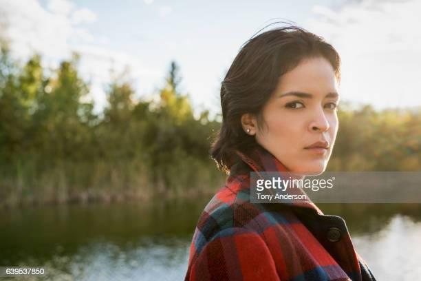Young hispanic woman near lake at sunset
