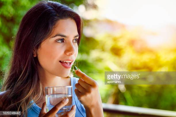young hispanic woman ready taking a pill with a glass of water in hand - taking a pill stock pictures, royalty-free photos & images