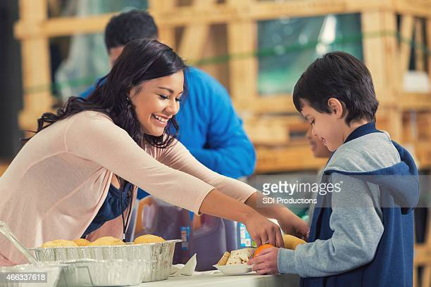 Young Hispanic woman serving meals in community soup kitchen