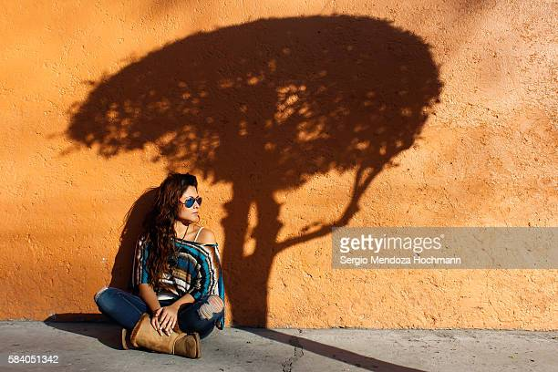 a young hispanic woman sitting by the shadow of a tree - characteristic of mexico photos et images de collection