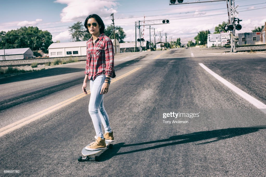 Young hispanic woman skateboarding on main street in a small town : Stock Photo