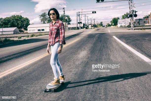 Young hispanic woman skateboarding on main street in a small town