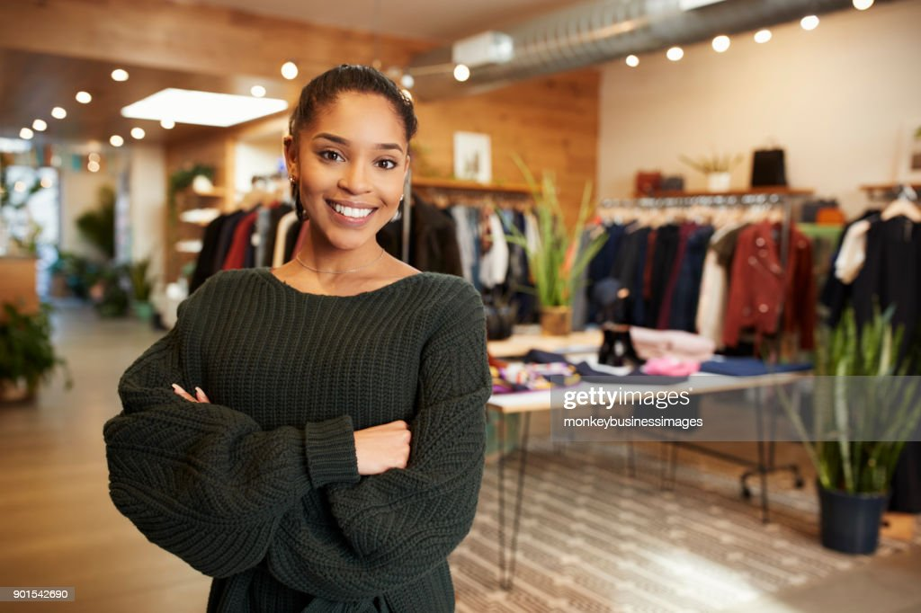 Young Hispanic woman smiling to camera in a clothes shop : Foto de stock