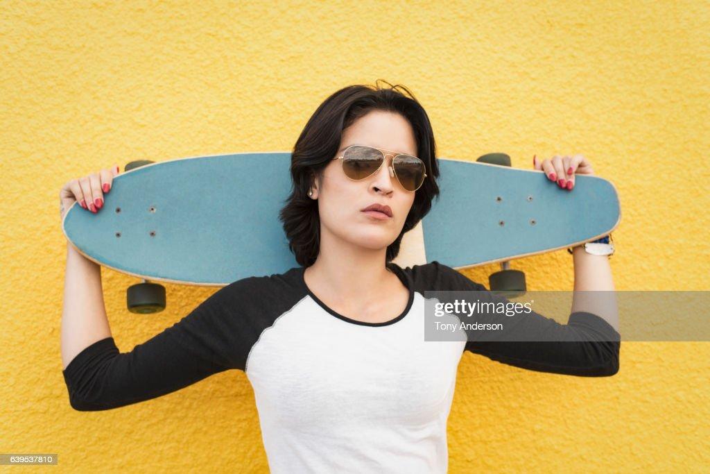 Young Hispanic woman standing near yellow wall with skateboard : Stock-Foto