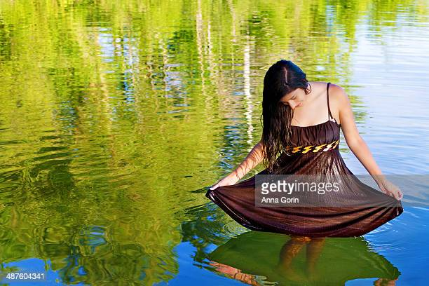 Young Hispanic woman stands in lake, curtsying