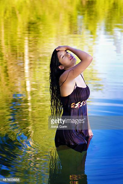 Young Hispanic woman stands in middle of lake