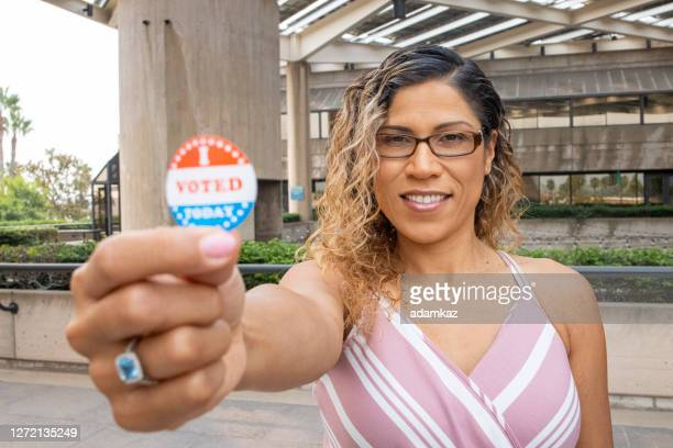 young hispanic woman with i voted sticker - midterm election stock pictures, royalty-free photos & images