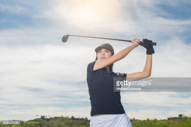 Young Hispanic Women Hitting A Golf Ball