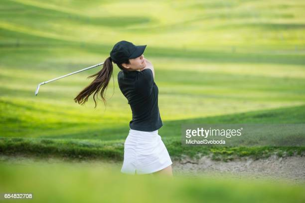 Young Hispanic Women Hitting The Ball Out Of A Bunker
