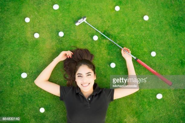 jungen hispanischen frauen legen auf dem putting green - golf lustig stock-fotos und bilder