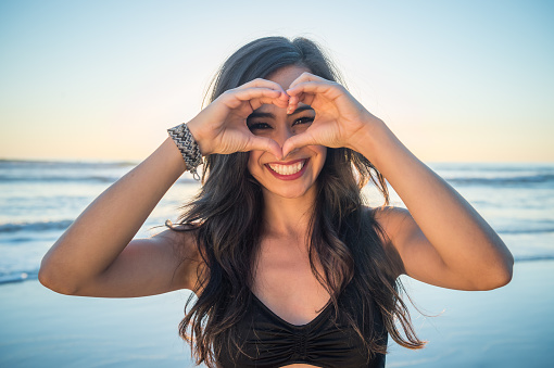 Young Hispanic Women On The Beach Heart Sign - gettyimageskorea