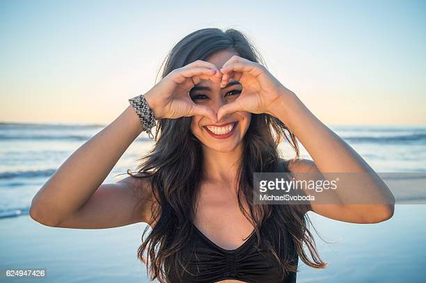 Young Hispanic Women On The Beach Heart Sign