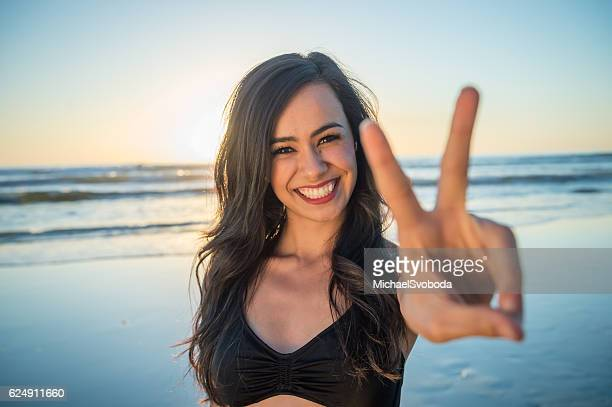 Young Hispanic Women On The Beach Peace Sign