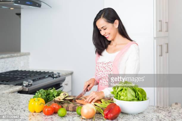 Jungen hispanischen Frauen eine Mahlzeit zuzubereiten